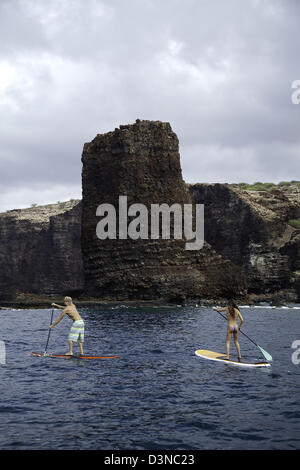 A young couple on stand-up paddle boards at Needles off the island of Lanai, Hawaii. Both are model released. - Stock Photo