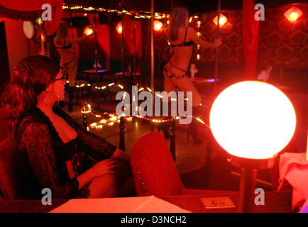 A Young Woman Dances In A Red Lit Tabledance Club Located