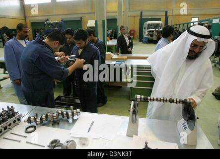 Apprentices measure pistons while a man dressed in traditional Arabic clothing observes a camshaft as part of the - Stock Photo