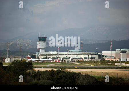 The photo shows the airport building, tower and runway of Olbia airport on the east coast of Sardinia, Italy, March - Stock Photo