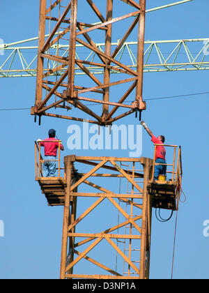 (dpa file) Two workers assemble a crane in Stuttgart, Germany, 29 March 2004. Photo: Juergen Effner Stock Photo
