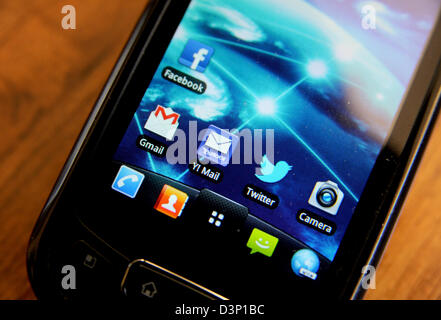 LG Mobile phone with Twitter Facebook GMail and Yahoo Mail apps on screen - Stock Photo