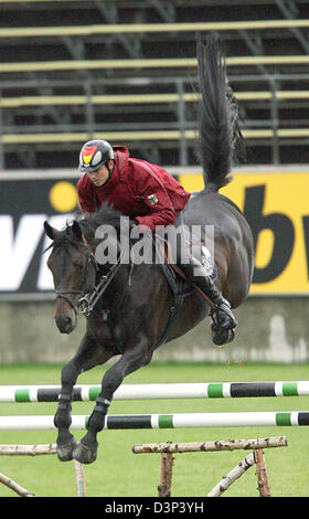 The German show jumper Marco Kutscher rides his horse 'Montender' during the practice session of the show jumpers - Stock Photo