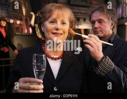 Sculptor Gottfried Krueger gives the finishing touches to his wax figure of Angela Merkel at the museum 'Panoptikum' - Stock Photo