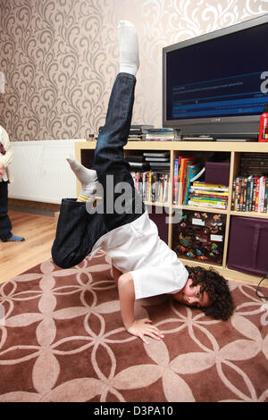 Young boy breakdancing in his living room. - Stock Photo