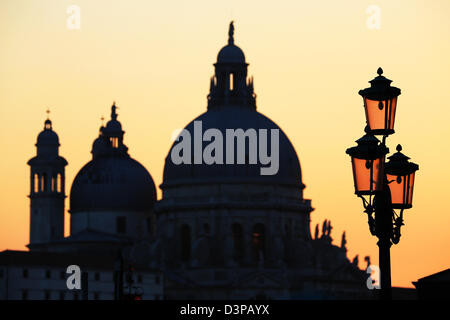 Silhouette of Santa Maria Della Salute and a lamp post at sunset in Venice, Italy - Stock Photo