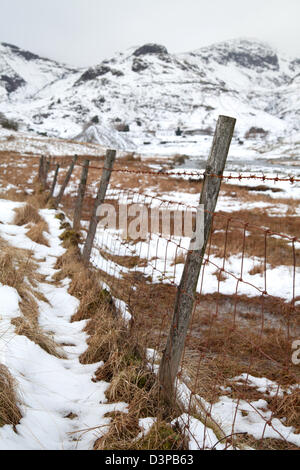 Old Barbed wire fence Coniston Copper Mines in winter with snow on the fells, Lake District, UK - Stock Photo