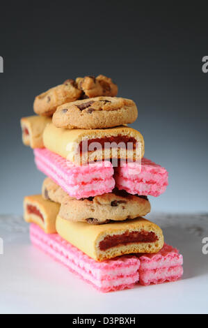 Closeup of a stack of assorted cookies with a light to dark background. Vertical format with shallow depth of field. - Stock Photo