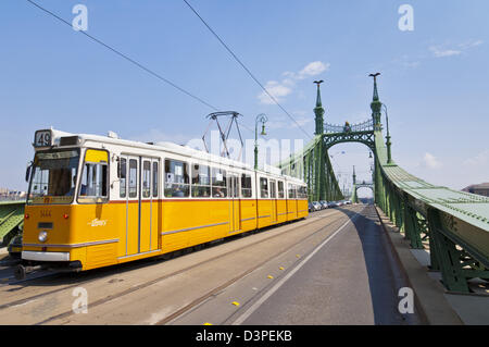 Yellow city tram crossing the Liberty bridge Budapest, Hungary, Europe, EU - Stock Photo