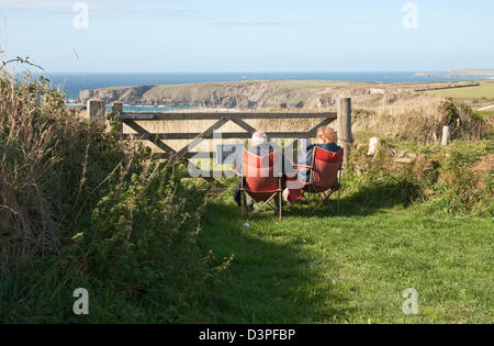 Couple peacefully reading in front of a gateway above Bedruthan Steps, Carnewas, between Newquay and Padstow, north - Stock Photo