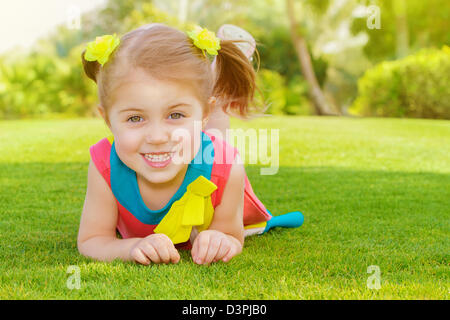 Picture of cute little girl lying down on green grass in park, cheerful child resting on the field on backyard, - Stock Photo