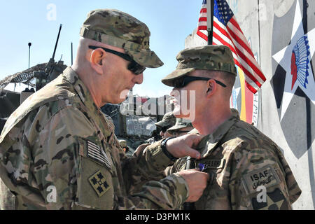 US Gen. Raymond Odierno, the Chief of Staff of the Army, pins Spc. Shawn Gravens with a Purple Heart February 22, - Stock Photo