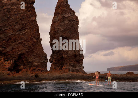 A couple on stand-up paddle boards at Needles off the island of Lanai, Hawaii. Both are model released. - Stock Photo