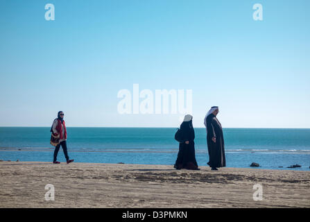 Arab family walking on beach, beside Mövenpick Hotel & Resort, Al Bida'a, Kuwait - Stock Photo