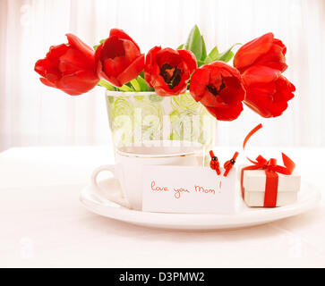 Photo of fresh red tulip flowers in beautiful vase on table, cup of tea, little white gift box with ribbon, festive - Stock Photo