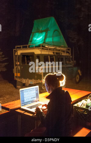 Woman working on laptop at campsite Sebago Lake Maine USA - Stock Photo