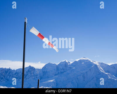 Windsock on a windy day at Les Grandes Platieres in Le Grand Massif with views to snowcapped Mont Blanc in French - Stock Photo