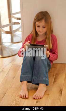 Young girl playing on an apple iPad tablet computer - Stock Photo
