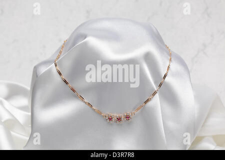 Close up photo of gold necklace on white textile