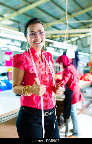 Female asian dressmaker or designer standing proudly in a textile factory, it is her workplace - Stock Photo