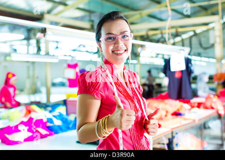 Female Chinese asian dressmaker or designer standing proudly in a textile factory, it is her workplace - Stock Photo