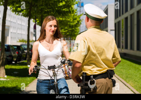 Police - young woman on bicycle with police officer in traffic control - Stock Photo