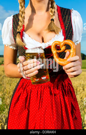 Young Bavarian woman drinking beer and keeping a pretzel in dirndl at meadow - Stock Photo