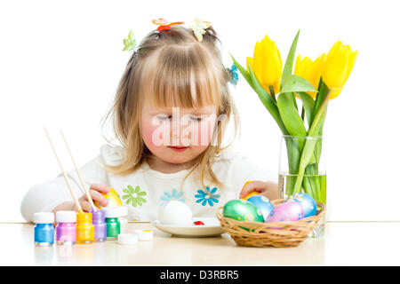 cute smiling baby girl painting Easter eggs isolated on white background - Stock Photo