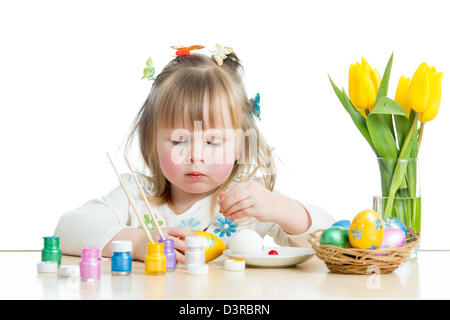 baby girl painting Easter eggs isolated on white background - Stock Photo