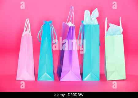 Group of colorful shopping paper bags standing on pink floor isolated on pink background - Stock Photo
