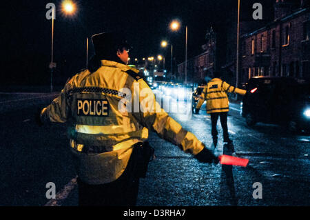 Two PSNI police officers direct traffic on a dark road at night after a serious accident - Stock Photo