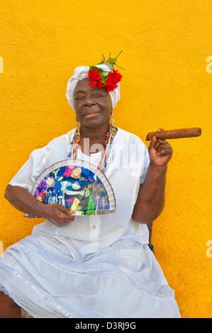 Cuban woman African descent wearing traditional Santeria white dress poses in Old Havana with cigar & fan in hand - Stock Photo