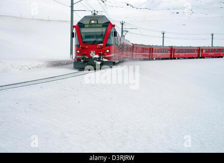 Mountain train at Lago Bianco Bernina Pass in Winter, Grisons, Switzerland   Eisenbahn am Lago Bianco am Bernina - Stock Photo