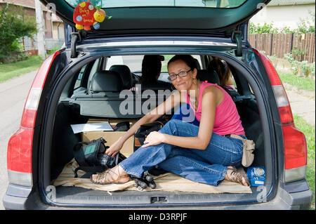 Cered, Hungary, a young woman sitting in the luggage room of a car - Stock Photo