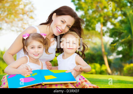 Image of cute young female with two little children read book outdoors, cheerful mother and two pretty kids sitting - Stock Photo
