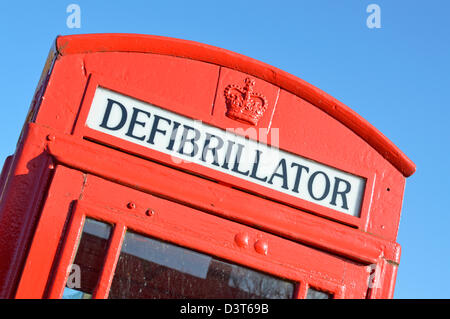 Red phone box converted for use as a publicly accessable defibrillator machine once telephone has been removed - Stock Photo