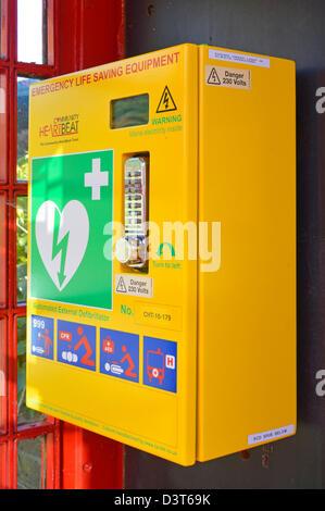 Heart attack emergency life saving defibrillator equipment housed inside redundant red K6 telephone phone box kiosk - Stock Photo