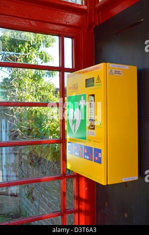Emergency defibrillator housed inside redundant red K6 telephone phone box kiosk located in the centre of a village - Stock Photo