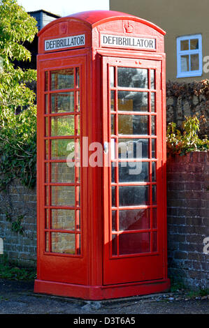 Defibrillator housed inside redundant red K6 telephone phone box kiosk located in the centre of a village community - Stock Photo