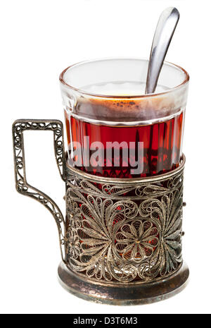 black tea in retro glass with teaspoon and glass-holder isolated on white background