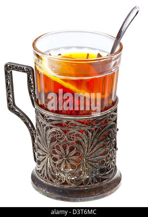 black tea with lemon in retro glass with teaspoon and glass-holder isolated on white background