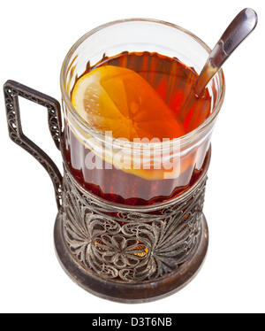 black tea with lemon in vintage glass with spoon and glass holder isolated on white background