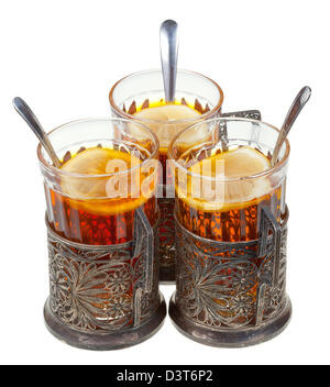 retro glasses in old silver glass holders with black tea and lemon isolated on white background