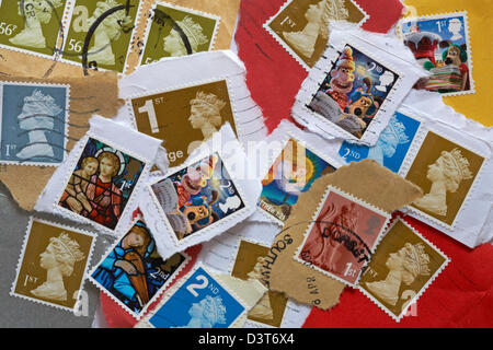 pile of used British postage stamps torn off envelopes and postcards - Stock Photo