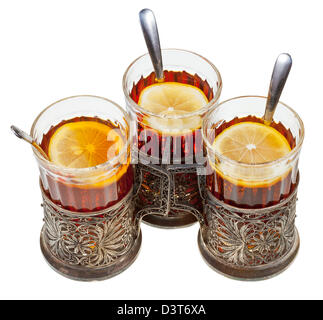 top view of three retro glasses in silver glass holders with black tea and lemon isolated on white background