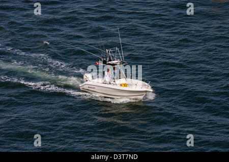 Two men heading out on blue water in a small white fishing boat - Stock Photo
