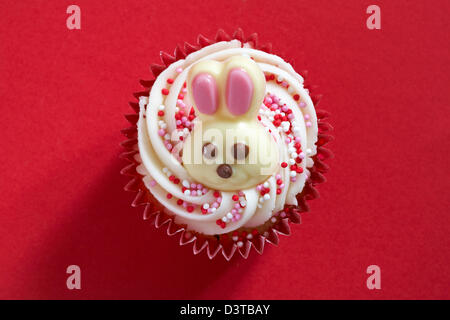 Easter cupcake with white chocolate bunny rabbit on isolated on red background - Stock Photo