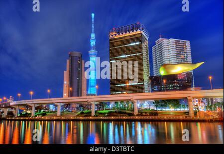 Landmark buildings line the Sumida River at Asakusa in Tokyo, Japan. - Stock Photo