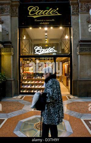Elegant elderly woman passing the chic Cade designer mens boutique in Galleria Vittorio Emanuele II Milan Lombardy - Stock Photo