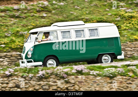 Green VW campervan on coastal road, St Agnes, Cornwall, UK - Stock Photo